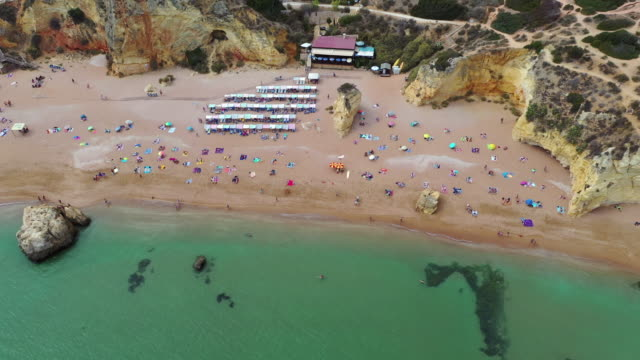 aerial panning shot of tourists at beach by rocky cliffs near sea, drone flying over people on shore - lagos, portugal - portugal stock videos & royalty-free footage
