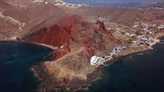 vidéos et rushes de aerial panning shot of tourists at famous red beach on sunny day, drone flying over sea near mountains - santorini, greece - santorin
