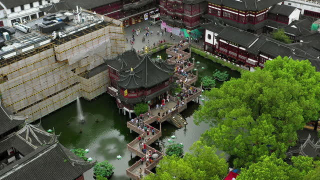 aerial panning shot of tourists at traditional building complex, drone flying forward over people in city - shanghai, china - bamboo plant stock videos & royalty-free footage