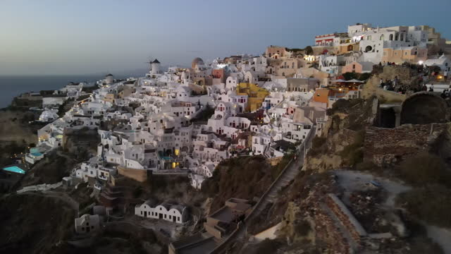 aerial panning shot of tourists in city on mountain against sky, drone flying over people on structure at sunset - santorini, greece - cyclades islands stock videos & royalty-free footage