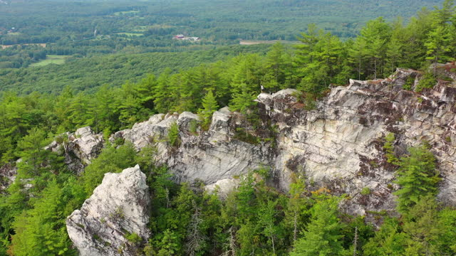 aerial panning shot of tourists moving down on rocky cliff amidst trees, drone flying over lush forest - berkshire county, massachusetts - massachusetts stock videos & royalty-free footage