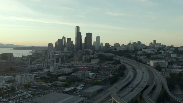 aerial panning shot of traffic on dr jose p rizal bridge by downtown, drone flying over modern cityscape by elliott bay against sky at sunset - seattle, washington - elliott bay stock videos & royalty-free footage