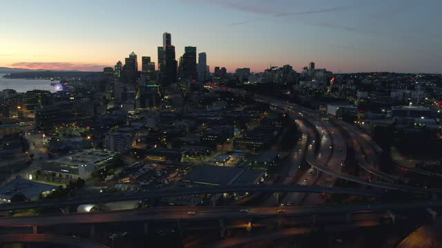 aerial panning shot of traffic on dr jose p rizal bridge in city at sunset, drone flying over modern cityscape by elliott bay against sky - seattle, washington - elliott bay stock videos & royalty-free footage