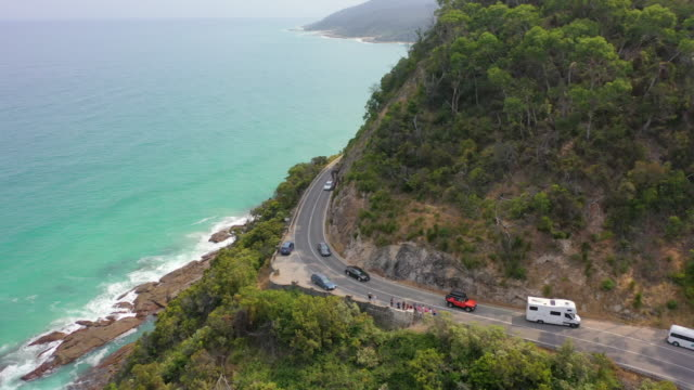 aerial panning shot of vehicles and people on road over cliff near sea, drone flying over green plants on sunny day - great ocean road, australia - great ocean road stock videos & royalty-free footage