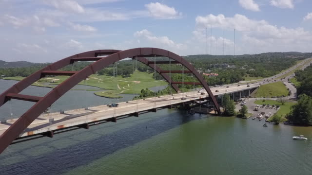 aerial panning shot of vehicles on arch bridge over river against sky, drone flying from left to right on sunny day - austin, texas - arch bridge stock videos & royalty-free footage