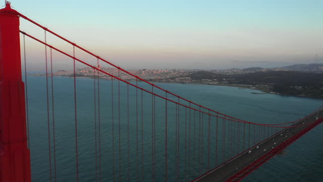 aerial panning shot of vehicles on golden gate bridge over bay, drone flying forward over famous landmark against sky at sunset - san francisco, california - san francisco california stock videos & royalty-free footage