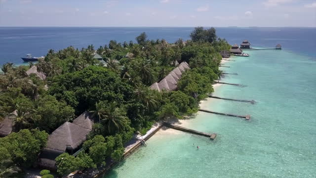 aerial panning shot of water bungalows at luxurious resort against sky, drone flying over tourists at hotel on sunny day - vaadhoo, maldives - malediven stock-videos und b-roll-filmmaterial