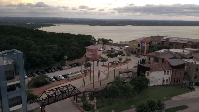 vídeos de stock e filmes b-roll de aerial panning shot of water tank by footbridge amidst buildings in city, drone flying from right to left over parking lot near river against sky during sunset - austin, texas - rio colorado