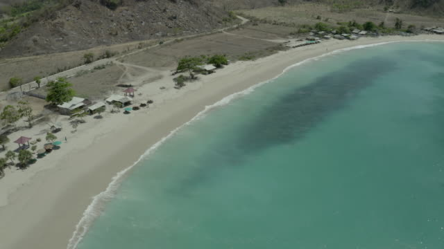 aerial panning shot of wave splashing on shore at beach during sunny day, drone flying over turquoise sea - lombok, indonesia - sunny video stock e b–roll