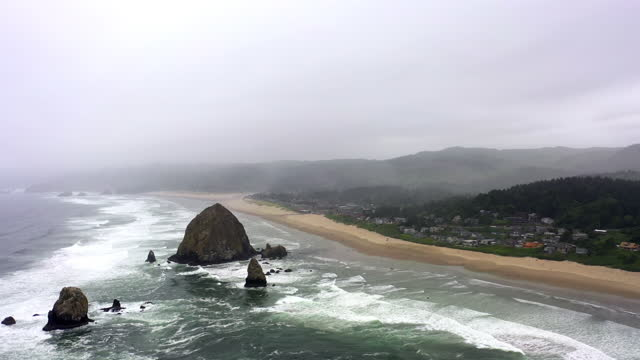 aerial panning shot of waves splashing at beach against cloudy sky, drone flying over coastline near city - cannon beach, oregon - oregon coast stock videos & royalty-free footage