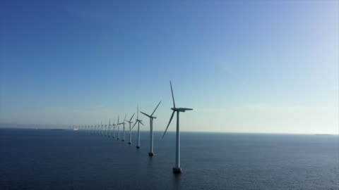 aerial panning shot of wind turbines in sea against blue sky, drone flying over water on sunny day - copenhagen, denmark - wind turbine stock videos & royalty-free footage