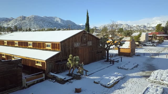 aerial panning shot of wooden structures in snow covered town, drone flying towards closed entrance on sunny day - joshua tree, california - joshua tree national park stock videos & royalty-free footage