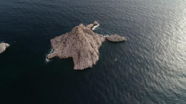 vidéos et rushes de aerial panning shot showing a rocky island off the coast of marseille, france - tourisme