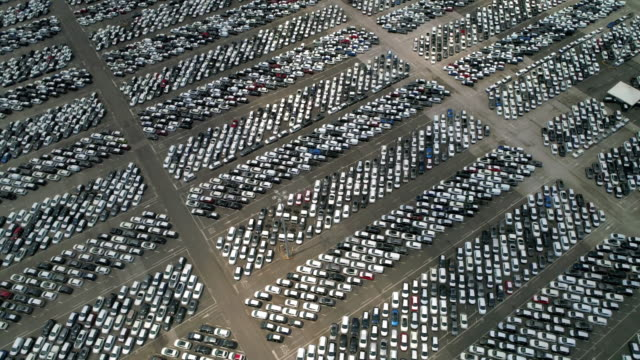 aerial panning shot showing a vast number of cars for sale, livorno, italy - parallele geometrie stock-videos und b-roll-filmmaterial