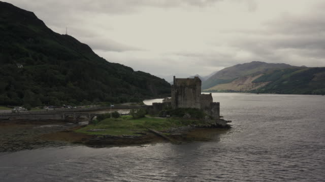 aerial panning shot showing eilean donan castle, scottish highlands, united kingdom - atmospheric mood stock videos & royalty-free footage
