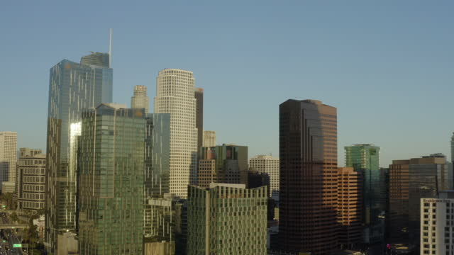 aerial panning the gleaming skyscrapers and downtown skyline with clear blue skies and bright sunlight reflecting off the building windows - los angeles, california - fensterfront stock-videos und b-roll-filmmaterial