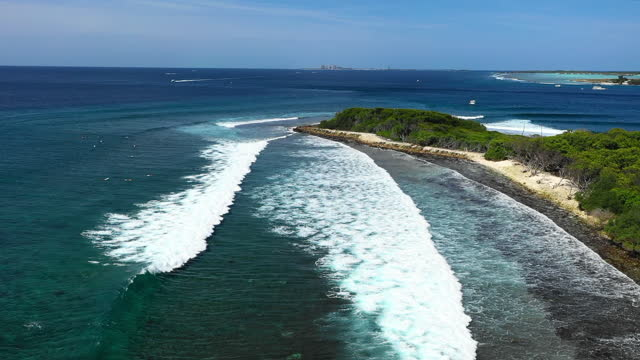 aerial panning the lush shoreline and crashing waves of a small tropical island with green palm trees, small boats moored nearby, and other islands visible in the distant horizon - thanburudhoo, maldives - other点の映像素材/bロール