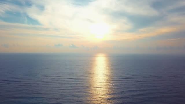 vídeos de stock, filmes e b-roll de aerial: panning towards the setting bright sun - inclinação para cima