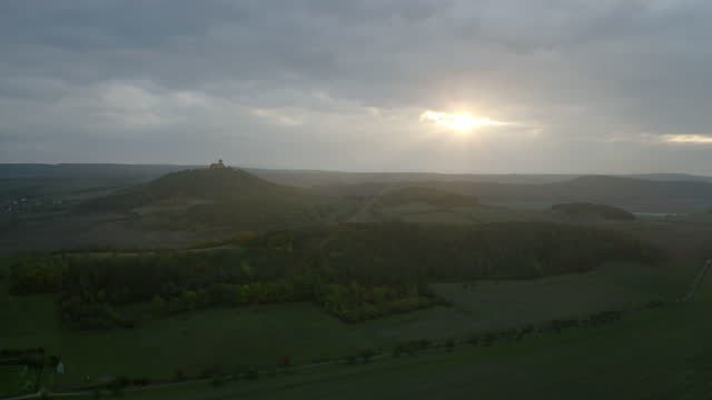 vidéos et rushes de aerial panning verdant green crop fields and valley at dawn with cloudy skies, rolling hills, and wachsenburg castle in the background - drei gleichen, germany - vallée