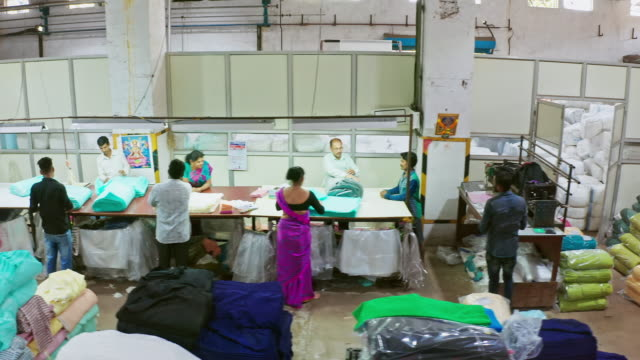aerial panning video of indian group of people working factory in the packaging area - textile stock videos & royalty-free footage