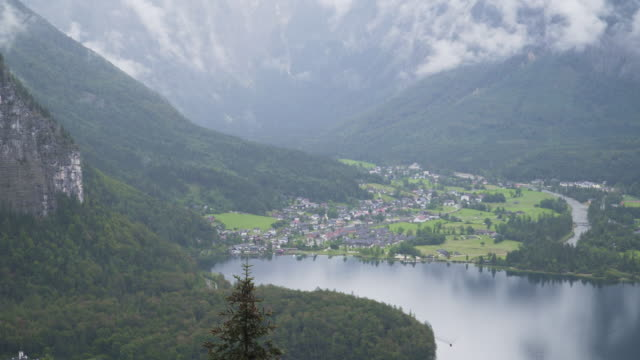 aerial panning view: beautiful hallstatt lakefronts small austrian village at the famous obertraun mountain covering fog of raining day in summer. concept of an international landmark of austria. - upper austria stock videos & royalty-free footage