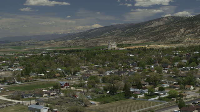 vídeos de stock, filmes e b-roll de aerial panning view of city in valley near mountains and temple / manti, utah, united states - utah