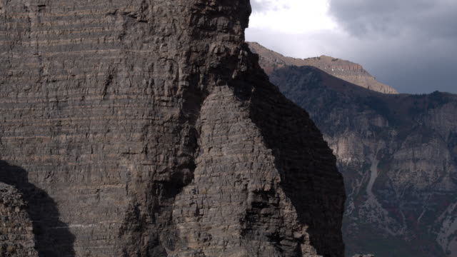 vidéos et rushes de aerial panning view of rocky cliff face revealing mountain - provo