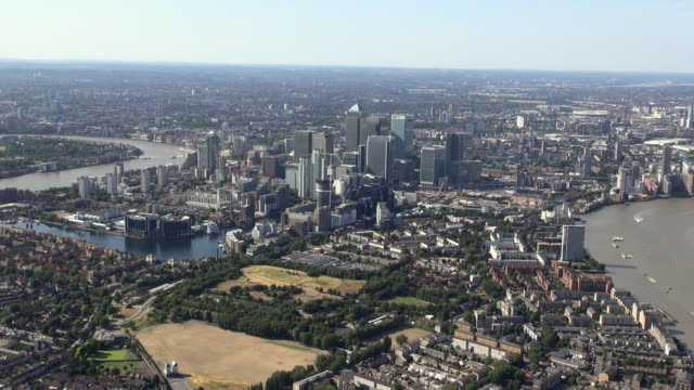 aerial panorama of east london zooming out from a close up view of canary wharf skyscrapers and taking in the isle of dogs, river thames, docklands and o2 arena - east london stock videos and b-roll footage