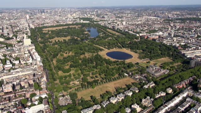 aerial panoramic video of kensington gardens and hyde park with round pond and the serpentine, zooming out to views over knightsbridge, westminster, bayswater, paddington, central london and beyond - the serpentine london stock videos & royalty-free footage