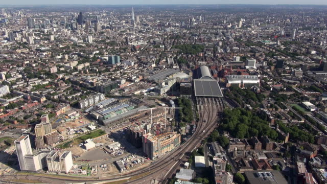 Aerial panoramic video of Kings Cross Central building development site, St Pancras International and Kings Cross railway stations and surrounding areas, with distant views south eastwards over the city and south east London