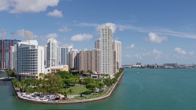 aerial panoramic view of biscayne bay around brickell key island, downtown miami, florida, on a sunny day. drone-made video clip with backward and wide orbiting-panning cinematic camera motion. - biscayne bay stock videos & royalty-free footage