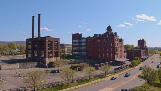 aerial panoramic view of the historic abandoned beer factory converted into the administrative center in wilkes-barre, pennsylvania, in spring.  drone-made footage with the panning camera motion. - wilkes barre stock videos & royalty-free footage