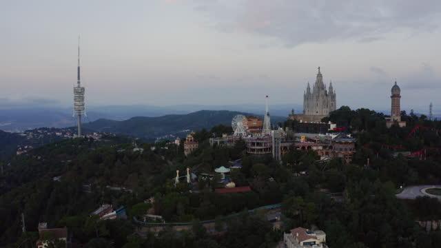 aerial panoramic view on barcelona's tibidabo mountain amusement park with collserola tv tower - basilica stock videos & royalty-free footage