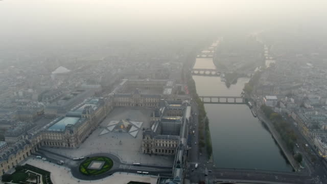 aerial: paris cityscape with river seine and louvre palace under hazy sky, france - river seine stock videos & royalty-free footage