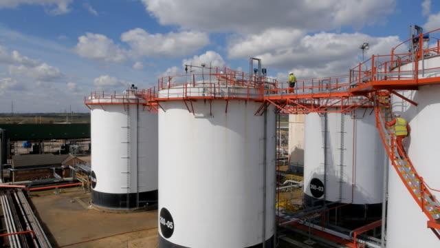 aerial pass along oil storage containers - fuel storage tank stock videos and b-roll footage
