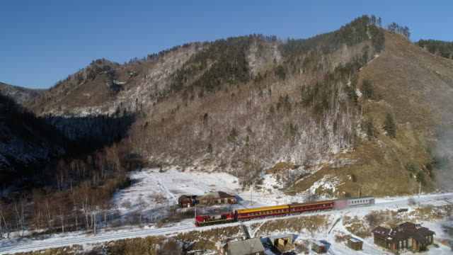 aerial: passenger train with people travels along mountain and steam - lake baikal, russia - russia stock-videos und b-roll-filmmaterial
