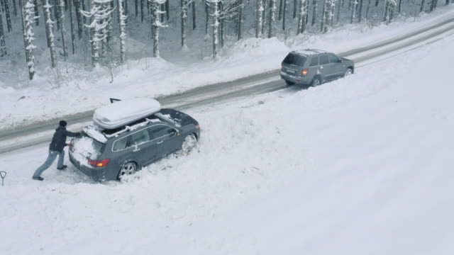 aerial passing driver helping by pushing a stuck car out of snow - spingere video stock e b–roll