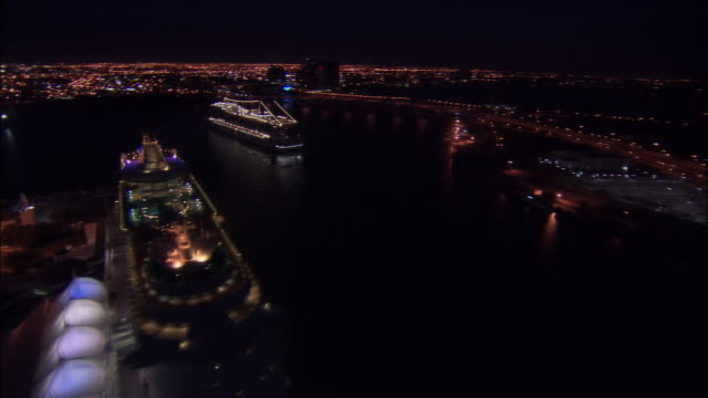 Aerial passing over cruise ships in Port of Miami at night / Miami, Florida