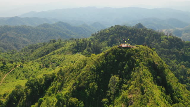 aerial: passing over doi thong viewpoint on highest mountain in pai, thailand - pai, thailand - temple body part stock videos and b-roll footage