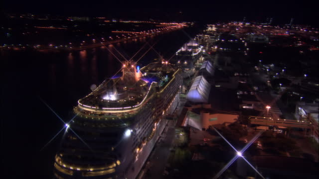 aerial passing over moored cruise ships in port of miami at night / miami, florida - passenger ship stock videos & royalty-free footage