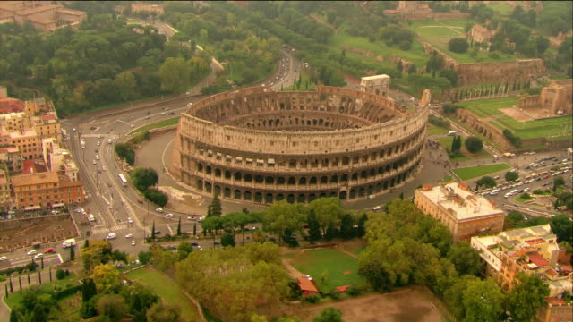 aerial passing over the colosseum as traffic goes around it / rome, italy - coliseum rome stock videos & royalty-free footage