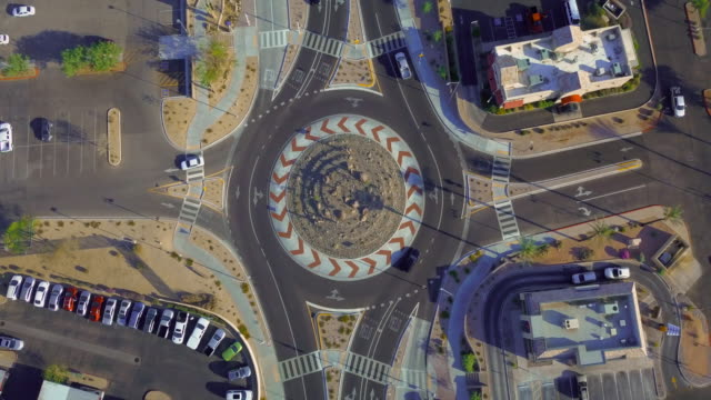 aerial: passing through the roundabout in arizona - road intersection stock videos & royalty-free footage