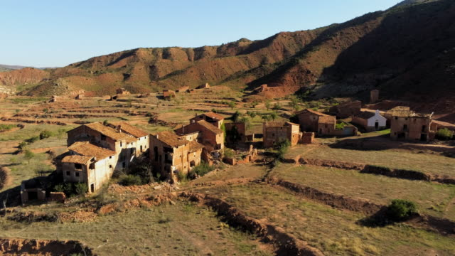 aerial past cluster of derelict houses in hills of abandoned village el campo, aragon - spanien stock-videos und b-roll-filmmaterial