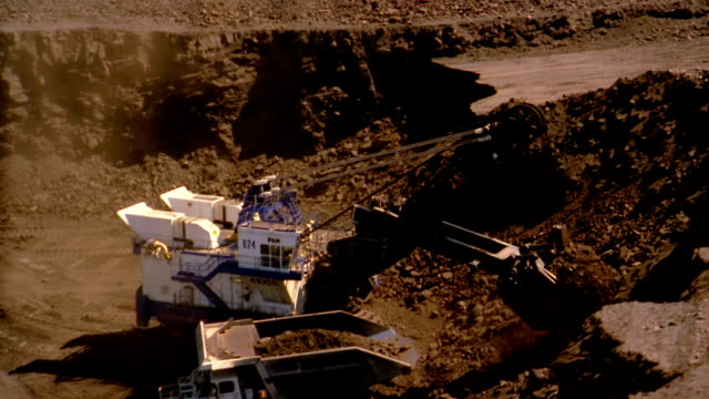 aerial past earth mover loading dump truck with coal in strip mine - 鉱業点の映像素材/bロール