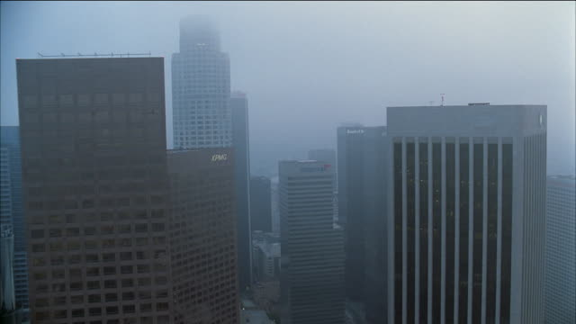 aerial past library tower, citigroup and bank of america buildings on foggy day / los angeles - 2002 stock videos & royalty-free footage