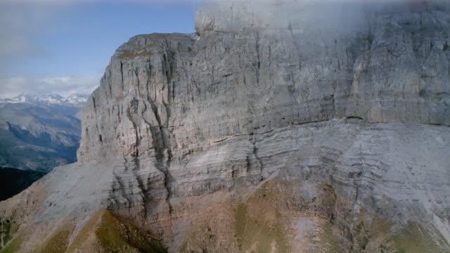 Aerial past mountainside to reveal snowcapped peaks / Spain