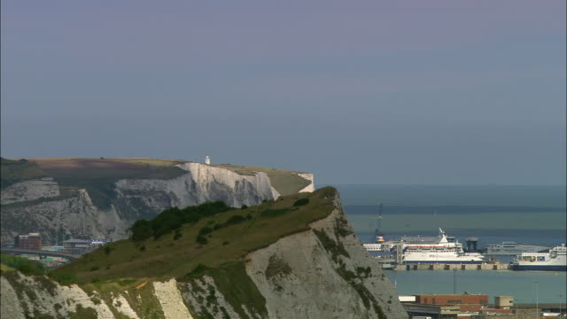 Aerial past the white cliffs of Dover to ships in Dover harbor /  Kent, England