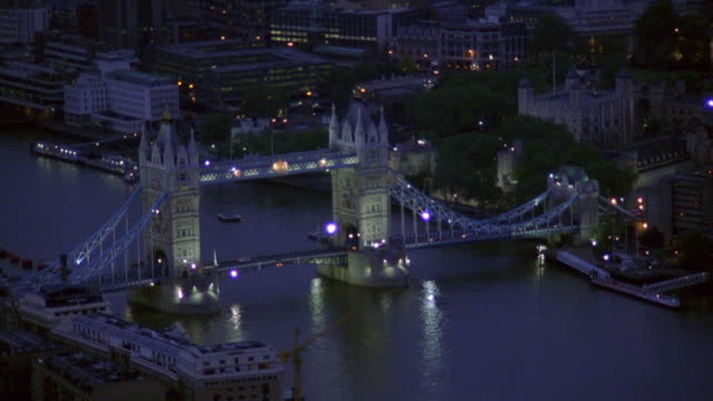 aerial past tower bridge at night / london - london bridge england stock videos & royalty-free footage