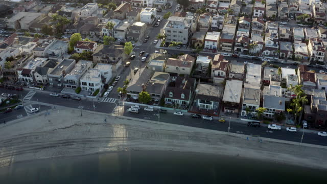aerial: patchwork of residential homes in golden sunshine on beach of turquoise ocean - long beach, california - patchwork stock videos & royalty-free footage