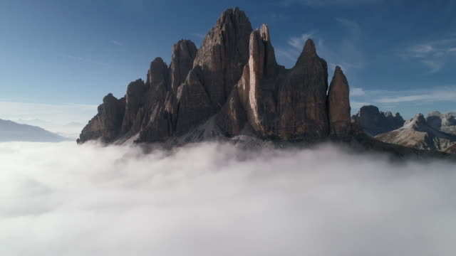 aerial pedestal shot of a mountain peak above the clouds, dolomites, italy - tre cimo di lavaredo stock videos & royalty-free footage